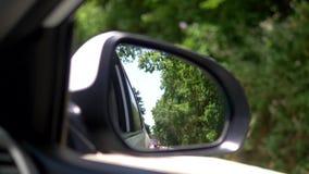 Concepto de la caza del coche Visi?n desde la ventanilla del coche en el espejo retrovisor es el perseguidor rojo visible del coc almacen de metraje de vídeo