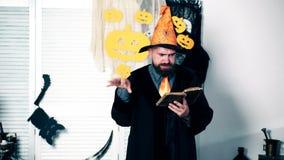 Concepto de la celebración de Halloween El mago lee el libro viejo y los gesticks con sus manos Magia de Halloween metrajes