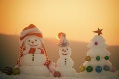 Concepto de la celebración de las vacaciones de invierno Los muñecos de nieve con las caras sonrientes en sombreros el la tarde a Imagenes de archivo