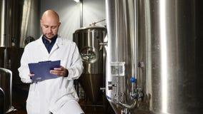 Concepto de la cervecería Escritura atenta del trabajador del mantenimiento en el tablero en la cervecería El empleado de los con metrajes