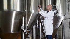 Concepto de la cervecería Escritura atenta del trabajador del mantenimiento en el tablero en la cervecería El empleado de los con almacen de video