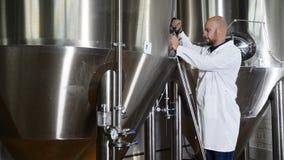 Concepto de la cervecería Escritura atenta del trabajador del mantenimiento en el tablero en la cervecería El empleado de los con almacen de metraje de vídeo