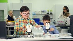 Concepto de la ciencia de la escuela Niños que miran en el microscopio, biología studing, química en laboratorio de la escuela Pr almacen de video