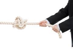 Mano del hombre de negocios que se sostiene o cuerda de tracción con el nudo atado Imagen de archivo