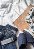 Concepto de la compra de la ropa del ` s de las mujeres Vaqueros, zapatillas de deporte, bufanda, bolsa de papel en un fondo lige Imagen de archivo libre de regalías