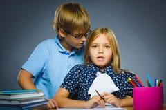 Concepto de la comunicación de la escuela muchacho que susurra en el oído de la muchacha Imagen de archivo