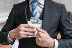 Concepto de la corrupción El hombre de negocios está ocultando la letra por completo del dinero o del soborno en chaqueta del tra Fotos de archivo