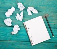 Concepto de la creatividad - libreta, lápiz y documento arrugado sobre azul imagen de archivo libre de regalías