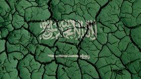 Concepto de la crisis: Grietas del fango con la bandera de la Arabia Saudita fotos de archivo