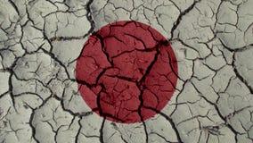 Concepto de la crisis política: Grietas del fango con la bandera de Japón fotografía de archivo libre de regalías