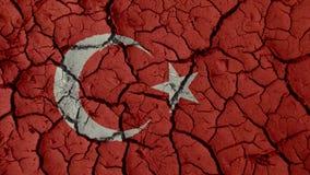 Concepto de la crisis política: Grietas del fango con la bandera de Turquía foto de archivo