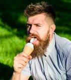Concepto de la delicadeza El hombre con la barba larga come el helado, mientras que se sienta en hierba Hombre barbudo con el con fotos de archivo