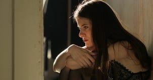 Concepto de la depresión La mujer joven con el pelo oscuro largo se sienta en el piso en ropa interior y gritos almacen de metraje de vídeo