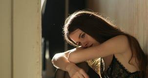 Concepto de la depresión La mujer joven con el pelo oscuro largo se sienta en el piso en ropa interior y gritos metrajes