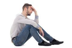 Concepto de la depresión - sentada subrayada del hombre aislada en blanco Imágenes de archivo libres de regalías