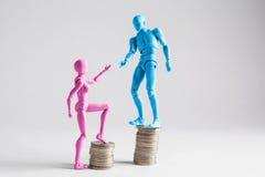 Concepto de la desigualdad de la renta mostrado con las estatuillas realistas y las pilas masculinas y femeninas de monedas Fotos de archivo