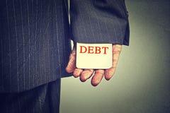 Concepto de la deuda tarjeta de ocultación de la deuda del hombre de negocios en una manga del traje Imágenes de archivo libres de regalías