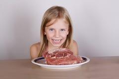 Concepto de la dieta del keto del carnívoro - pequeña muchacha rubia que come la carne cruda imagenes de archivo