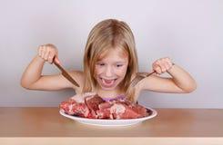 Concepto de la dieta del keto del carnívoro - pequeña muchacha rubia que come la carne cruda imágenes de archivo libres de regalías