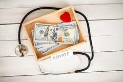 Concepto de la donación Caja con los dólares en el fondo blanco donaciones De alta resolución imagen de archivo libre de regalías