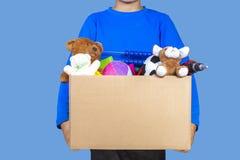 Concepto de la donación El sostenerse del niño dona la caja con ropa, libros y juguetes fotos de archivo libres de regalías