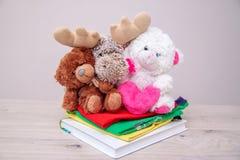 Concepto de la donaci?n Done la caja con ropa de los niños, libros, fuentes de escuela y juguetes Oso de peluche con el corazón r fotos de archivo