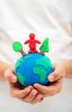 Concepto de la ecología con el globo del mundo de la arcilla en mano del niño fotografía de archivo