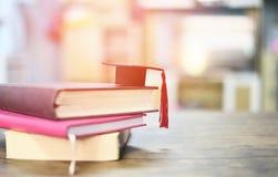 Concepto de la educaci?n con el casquillo de la graduaci?n en un libro en la tabla de madera foto de archivo libre de regalías