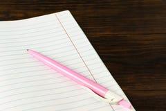 Concepto de la educación de nuevo a la escuela - pluma rosada en el primer del fondo del libro, maqueta, espacio de la copia imagen de archivo