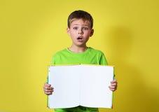 Concepto de la educación Shocked sorprendió al muchacho que sostenía el libro con el espacio vacío de la copia Imágenes de archivo libres de regalías