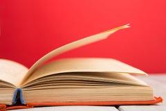 concepto de la educación y de la sabiduría - libro abierto en la tabla de madera, fondo del color Fotos de archivo libres de regalías