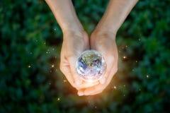 Concepto de la energía del ahorro, mano que sostiene la tierra contra la naturaleza imagen de archivo