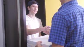 Concepto de la entrega de la pizza el muchacho adolescente entrega una caja de pizza de la forma de vida vídeo de la cámara lenta almacen de video