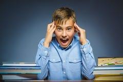 Concepto de la escuela duda o muchacho enojado que se sienta en el escritorio Imagen de archivo libre de regalías
