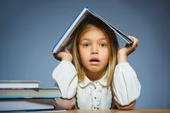 Concepto de la escuela dude a la muchacha que se sienta en el escritorio y que sostiene el libro en su cabeza Imágenes de archivo libres de regalías