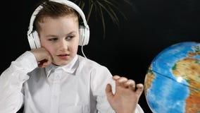 Concepto de la escuela El muchacho lindo se sienta en un escritorio con el globo en él y una pizarra detrás de él el colegial abu almacen de metraje de vídeo