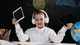 Concepto de la escuela El muchacho lindo se sienta en un escritorio con el globo en él y una pizarra detrás de él colegial positi almacen de metraje de vídeo