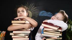 Concepto de la escuela El muchacho lindo y la muchacha atractiva se sientan con los montones de libros Los alumnos se sientan por almacen de video