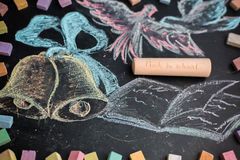 Concepto de la escuela en campanas y el cuaderno dibujados de la tiza de pizarra Foto de archivo