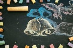 Concepto de la escuela en campanas y el cuaderno dibujados de la tiza de pizarra Fotos de archivo libres de regalías