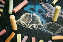 Concepto de la escuela en campanas y el cuaderno dibujados de la tiza de pizarra Fotografía de archivo libre de regalías