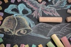 Concepto de la escuela en campanas y el cuaderno dibujados de la tiza de pizarra Foto de archivo libre de regalías