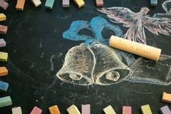 Concepto de la escuela en campanas y el cuaderno dibujados de la tiza de pizarra Imagenes de archivo