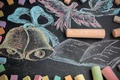 Concepto de la escuela en campanas y el cuaderno dibujados de la tiza de pizarra Fotografía de archivo