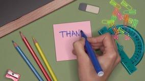 Concepto de la escuela La escritura de la mano de la mujer LE AGRADECE en la libreta metrajes