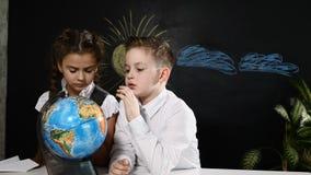Concepto de la escuela Los alumnos se sientan en un escritorio que juega con un globo en él Los niños se divierten que señalan al almacen de video