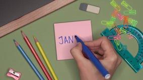 Concepto de la escuela La mano de la mujer que escribe ENERO en la libreta almacen de metraje de vídeo