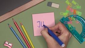Concepto de la escuela La mano de la mujer que escribe JULIO en la libreta almacen de video