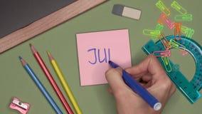 Concepto de la escuela La mano de la mujer que escribe JUNIO en la libreta almacen de video