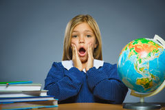 Concepto de la escuela muchacha con la expresión asombroso o de la duda que se sienta en el escritorio Imagenes de archivo